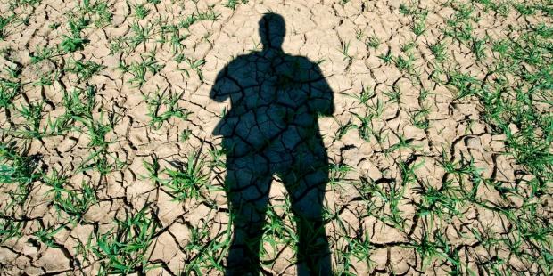 Una sombra humana se proyecta en la resquebrajada y árida tierra de un campo agrario. EFE